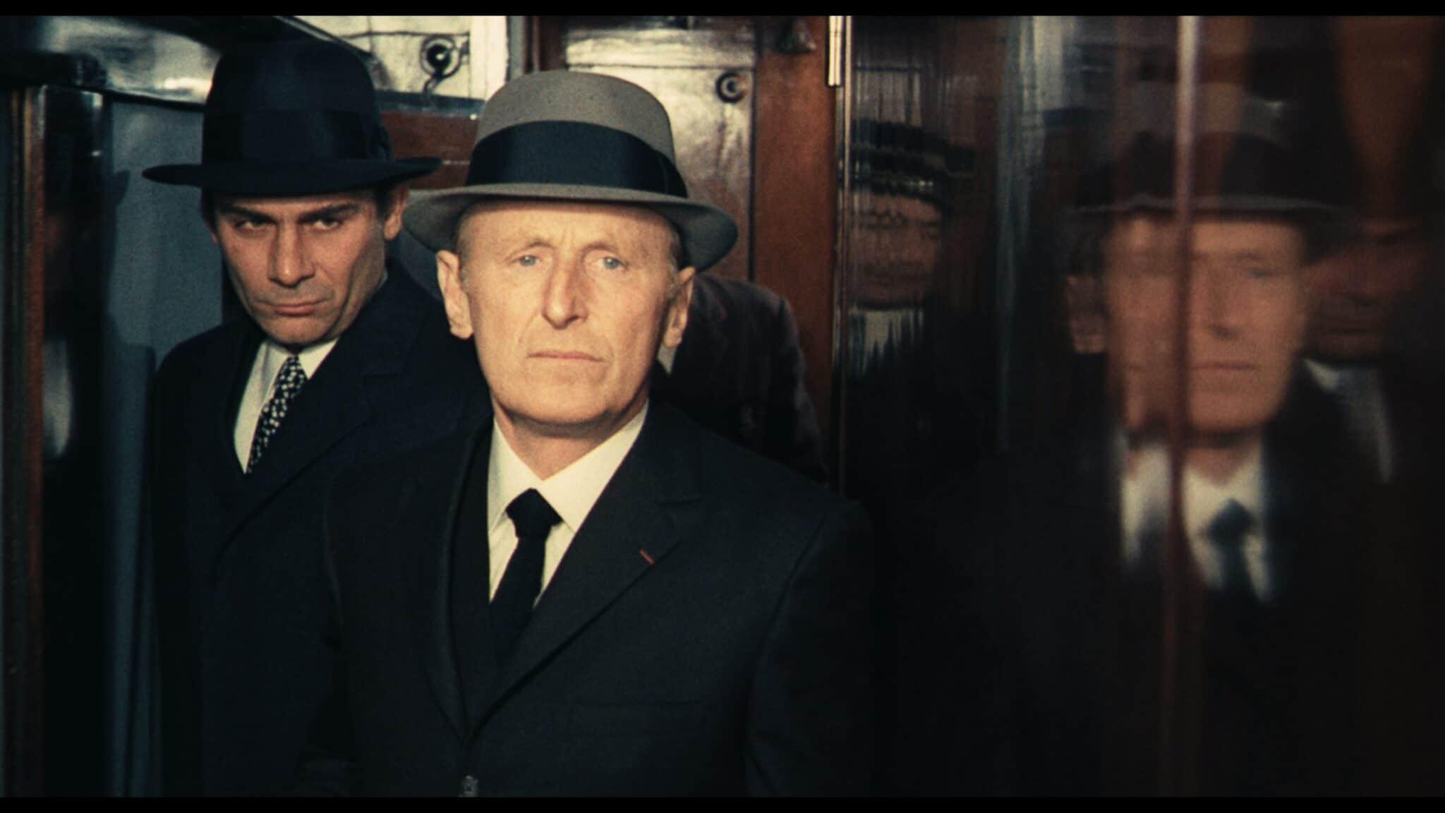 """Mattei (André Bourvil) führt Vogel (Gian Maria Volonté) in """"Vier im roten Kreis"""" durch den Gang des Zuges. Beide tragen schwarze Anzüge mit Mänteln und einen Hut."""