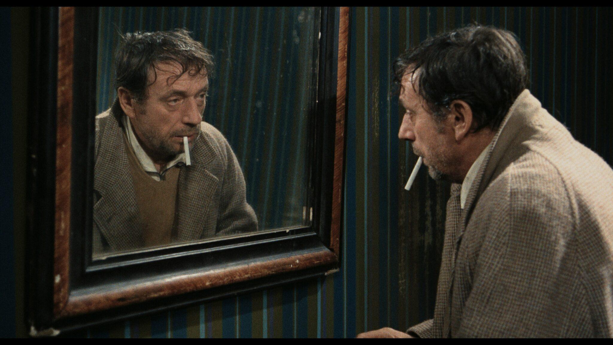 """Jansen (Yves Montand) guckt in """"Vier im roten Kreis"""" stark alkoholisiert in den Spiegel in seiner spärlichen Wohnung. Er zündet sich gerade eine Zigarette an."""