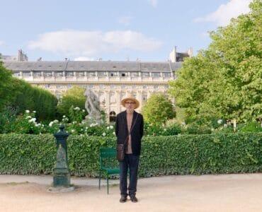 Elia Suleiman steht in einem dunklen Anzug und seinem Strohhut vor einer Grünanlage direkt vor einem alten, französischen Gebäude. Hinter ihm steht ein grüner Metallstuhl und ein grüner barocker Wasserspender. Er beobachtet etwas in der Ferne.