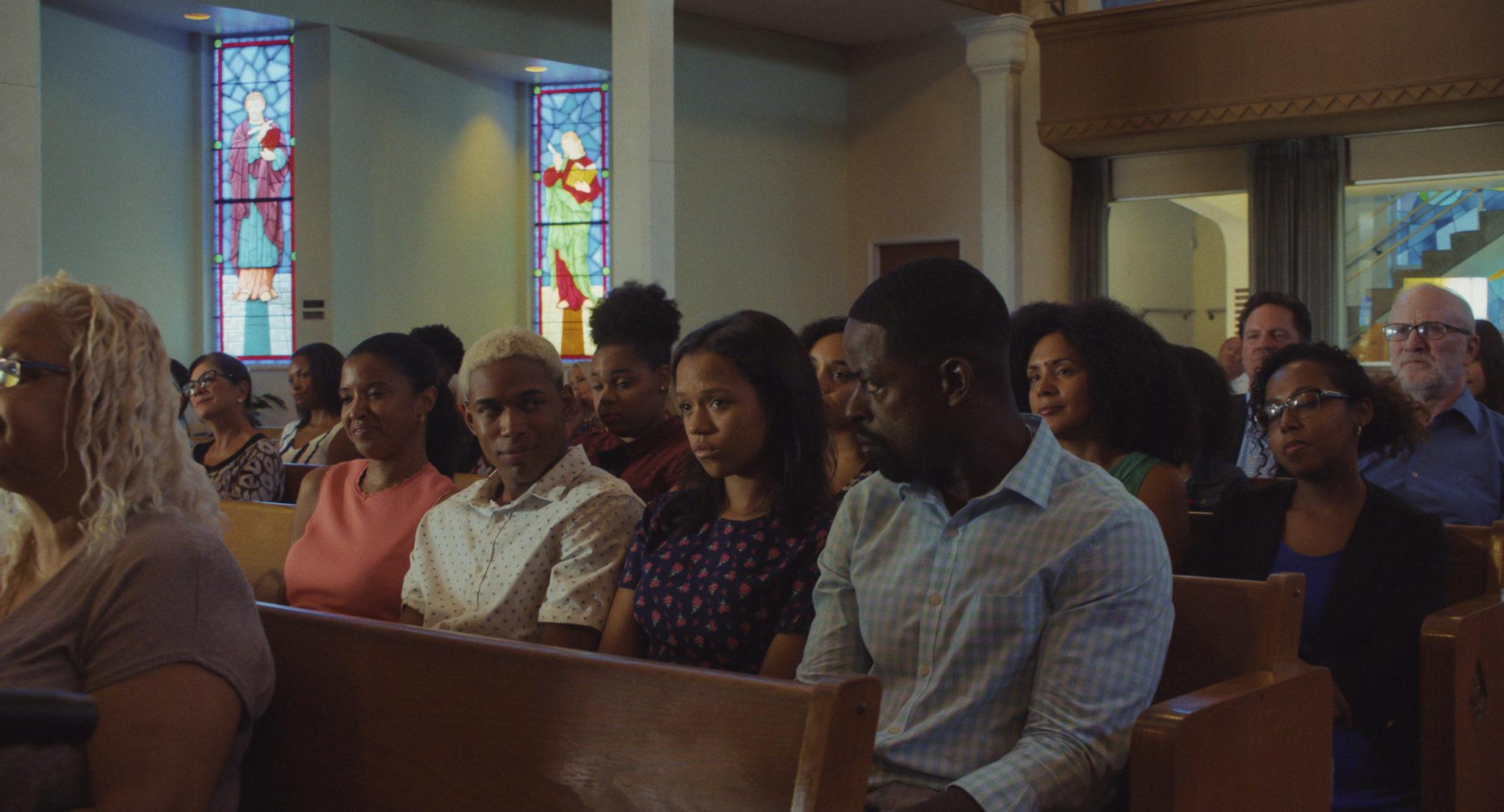 Die Familie Williams (bestehend aus Mutter, Vater, Sohn, Tochter) sitzt nebeneinander auf einer Kirchenbank und nimmt an einem Gottesdienst teil.