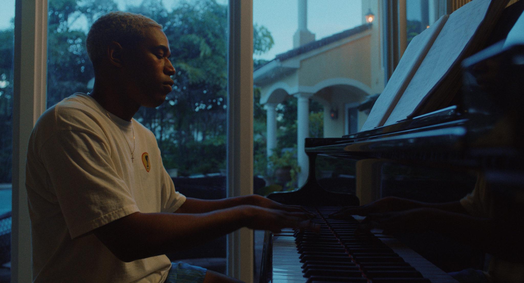 Tyler spielt das Klavier. Er trägt Freizeit Klamotten und im Hintergrund dämmert es.