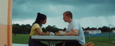 Emily sitzt mit ihrem Freund draußen an einem Tisch. Der Himmel ist bewölkt und es wirkt regnerisch.