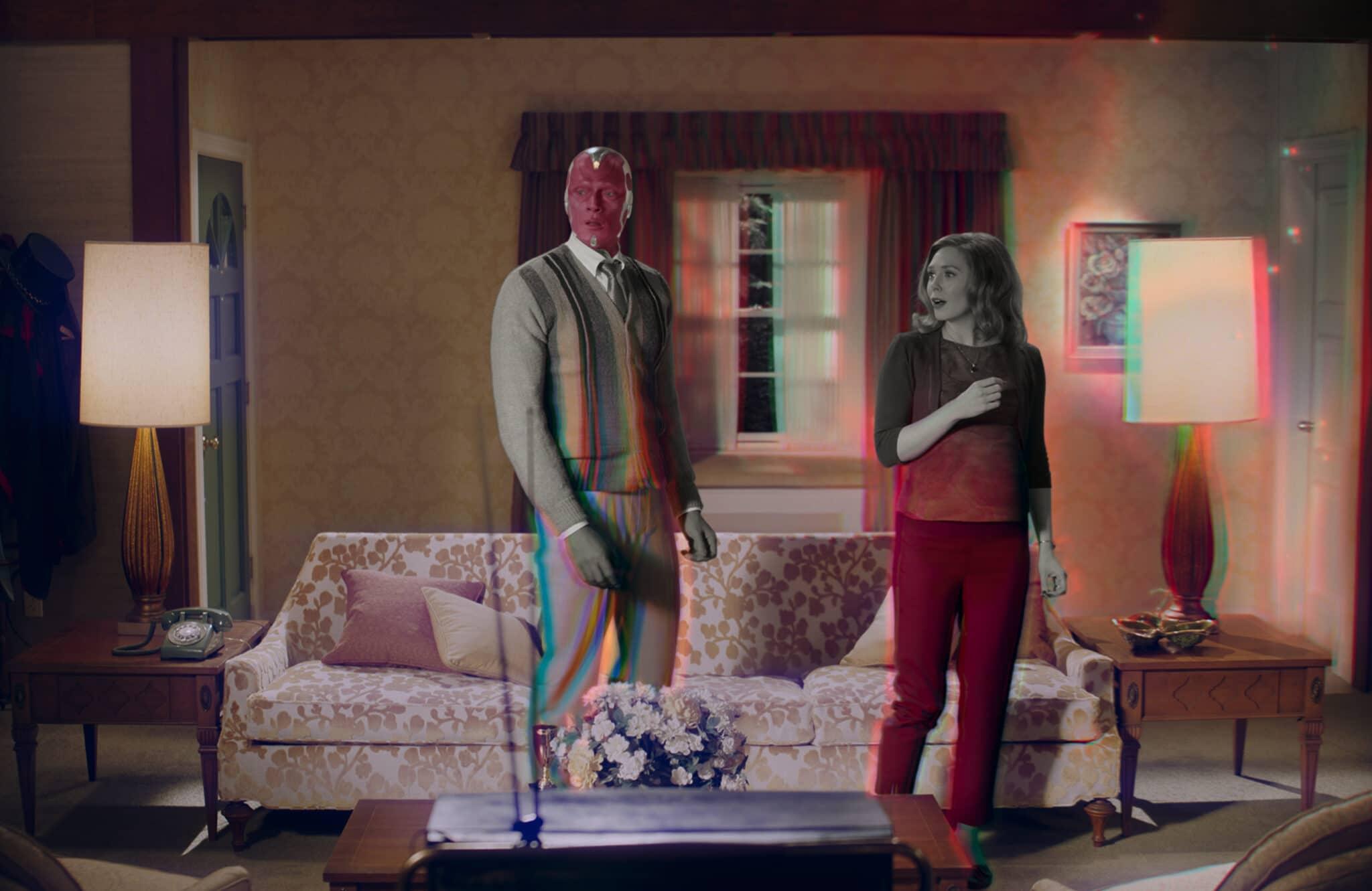 Vision (Paul Bettany) und Wanda (Elizabeth Olsen) stehen in biederer Kleidung in einem Sechzigerjahre-Wohnzimmer vor einem Blumenmustersofa. Außerdem sieht man zwei Stehlampen, ein altes Telefon und ein Blumengesteck.