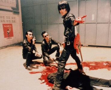 Guitar Wolf hat eine goldene Kugel in einer Zombie-Leiche gefunden, die blutig auf dem Boden einer Garage liegt - Wild Zero