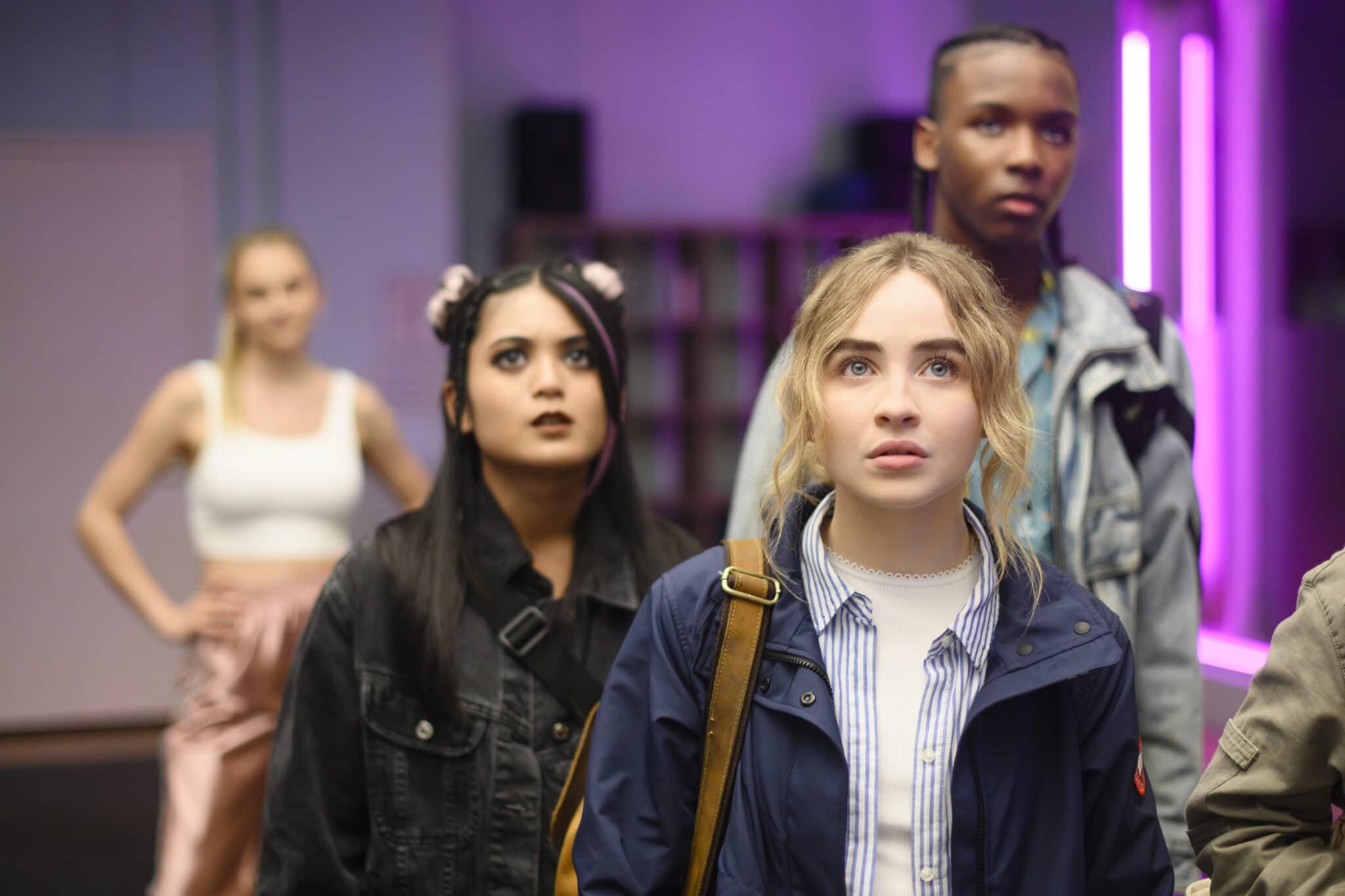 Im Vordergrund steht Sabrina Carpenter als Quinn Ackerman, dahinter leicht unscharf Bianca Asilo als Raven und Nathanielle Scarlette als DJ Tapes