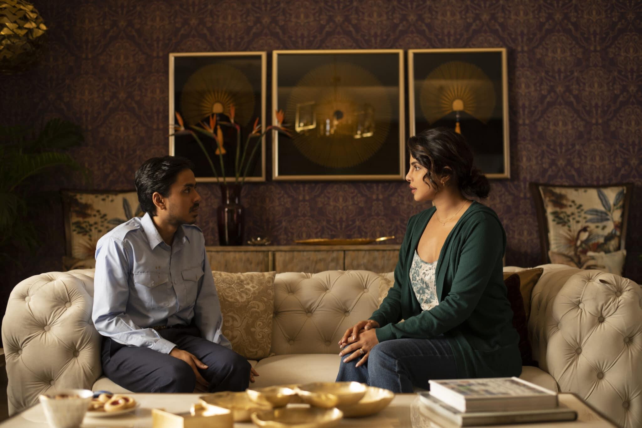 Balram (Adarsh Gourav) sitzt seiner Herrin (Priyanka Chopra) auf einem noblem weißen Sofa gegenüber. Im Hintergrund sieht man eine gemustert tapezierte Wand mit drei Bildern in goldenem Rahmen.