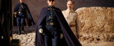 """Johnny Depp und Markt Rylance in """"Waiting for the Barbarians"""" spielen die vermeintlichen Widersacher in diesem Drama. Depp marschiert in seiner dunklen Kleidung, um die er zusätzlich einen Umhang trägt, auf den Betrachter zu. Durch seine Sonnenbrille sind keinerlei Emotionen zu erkennen. Hinter ihm geht Rylance in seiner beigen Kleidung her. Er blickt etwas zerknirscht auf den vor ihm gehenden Depp."""