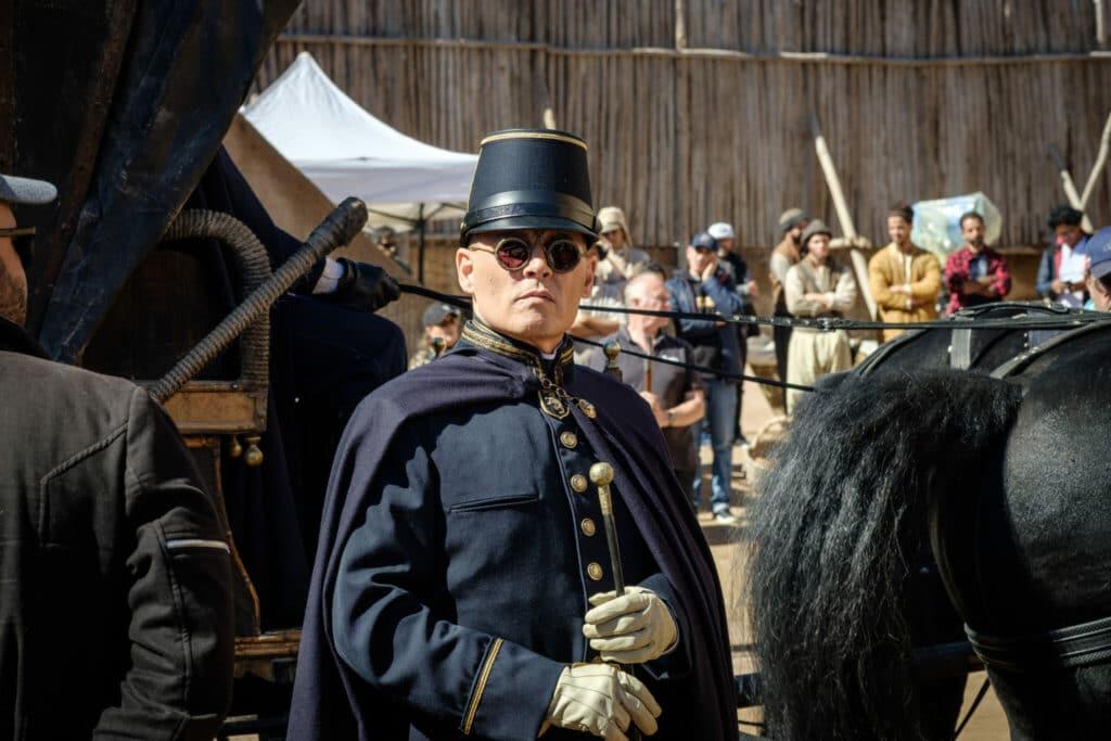"""Johnny Depp als gnadenloser Colonel Joll in """"Waiting for the Barbarians"""". Er trägt die dunkelblaue Militärkleidung dieser Zeit. Durch seine Sonnenbrille sind keinerlei Emotionen zu erkennen. Hinter ihm ist eine Kutsche leicht zu erkennen sowie der Schweif und die Hinterläufer des davor gespannten Pferds. Im Hintergrund sind zudem mehrere Leute zu erkennen."""