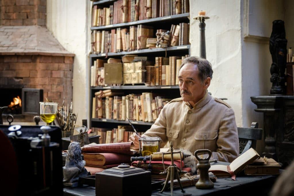 """Mark Rylance spielt den sanftmütigen Magistrat in """"Waiting for the Barbarians"""". Dieser sitzt in seinem Quartier am Schreibtisch und scheint etwas zu schreiben. Sein Blick geht allerdings in eine andere Richtung. Vermutlich zur Tür des Raums oder jemanden der gegenüber des Schreibtischs steht. Im Hintergrund ist ein großes in die Wand eingelassenes Regal mit vielen Büchern und Schriftrollen zu sehen."""