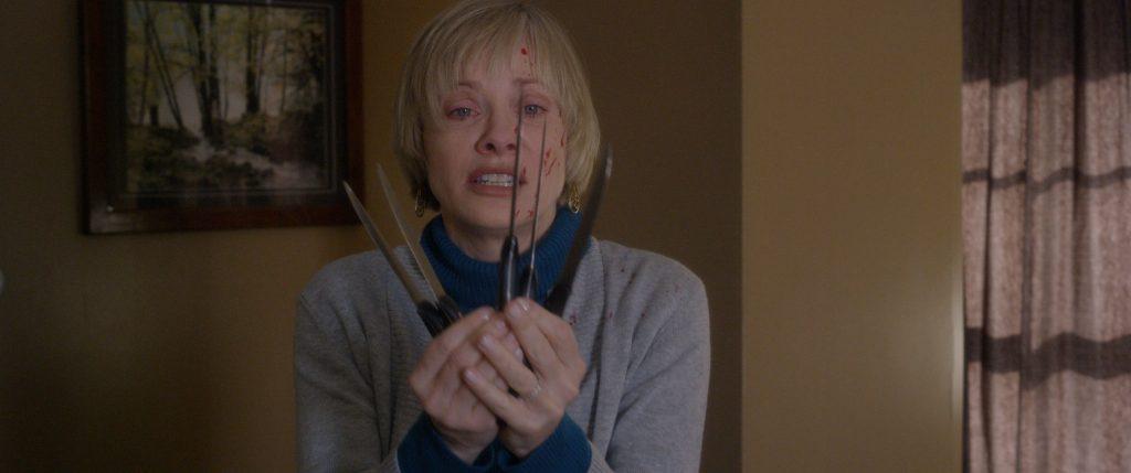 Die blutbefleckte Anne (Barbara Crampton) hält ängstliche mehrere Messer vor sich.