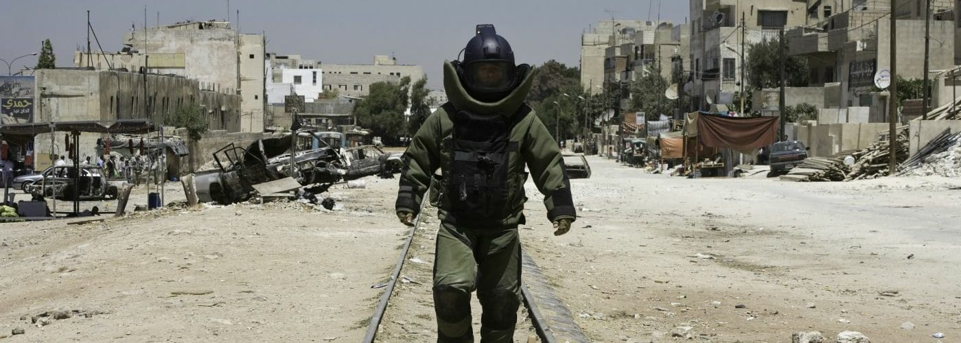 Ein Soldat im Schutzanzug läuft in einem menschenleeren Gebiet auf Zuggleisen auf die Kamera zu