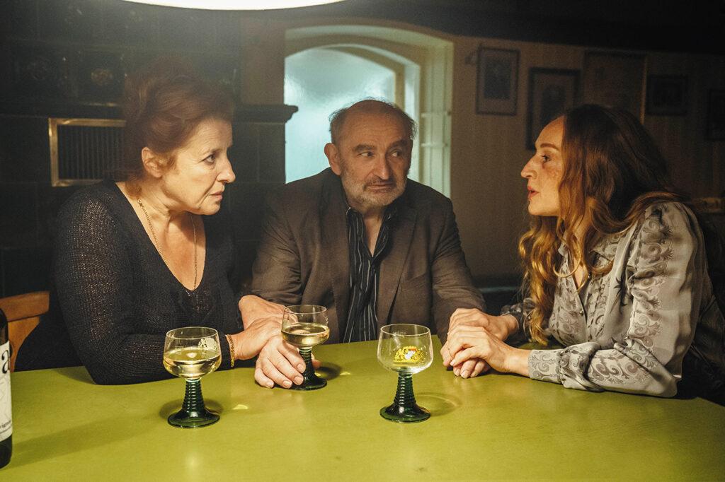 Gerda (Luise Kinseher) und Dr. März (Brigitte Hobmeier) buhlen um die Aufmerksamkeit des Kommissars, indem sie ihn an seinen Unterarmen packen. Alle trinken im Wirtshaus Alkohol.