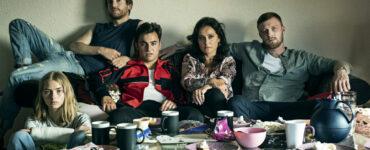 Die ganze Familie sitzt auf der Coch vor einem gedeckten Tisch und schaut in die Kamera.