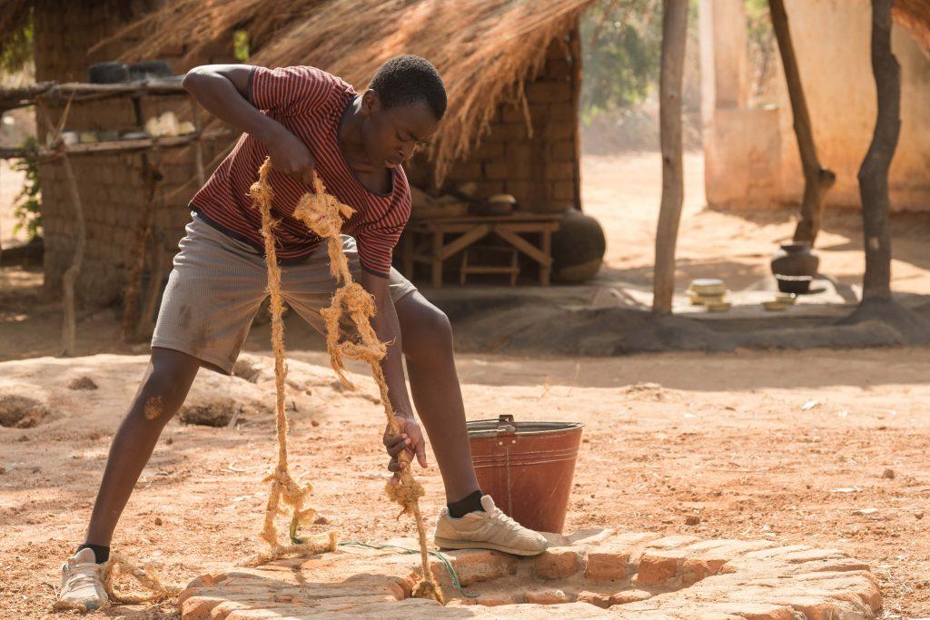 William (Maxwell Simba) hilft bei der Arbeit im Dorf ©Netflix