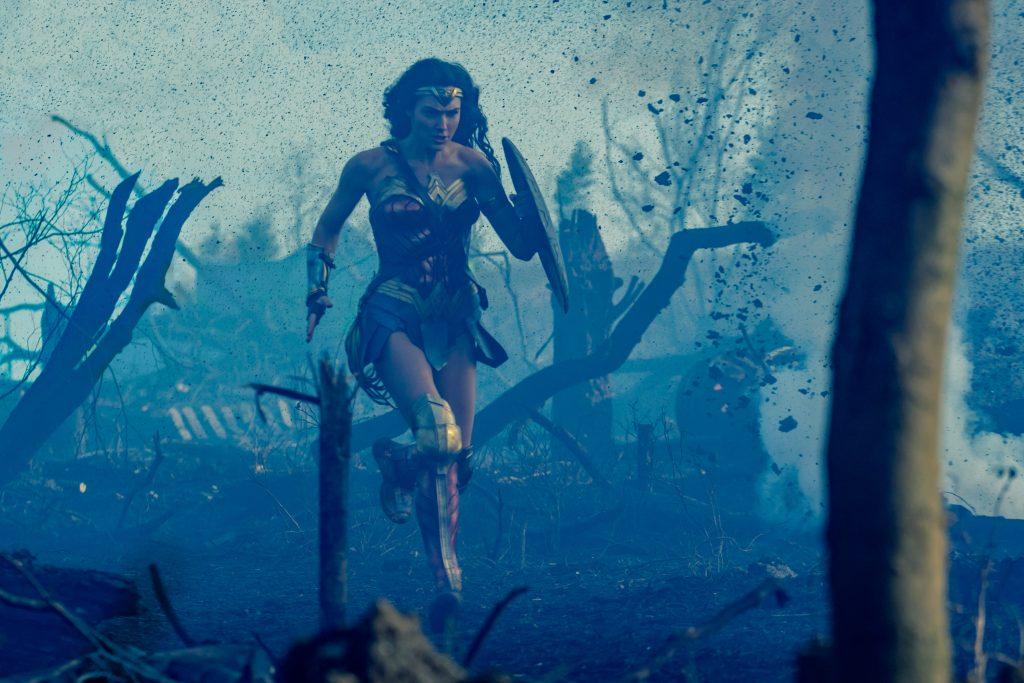 Wonder Woman rennt mit ihrem Schild über ein Schlachtfeld, während Explosionen Erde in die Luft schleudern