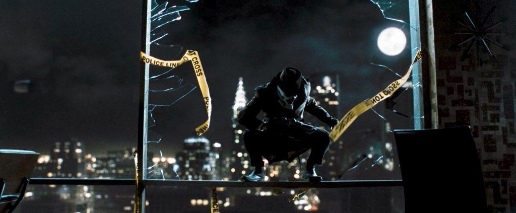 Rorschach kauert auf einem Geländer, mitten in der Nacht, um ihn Absperrband