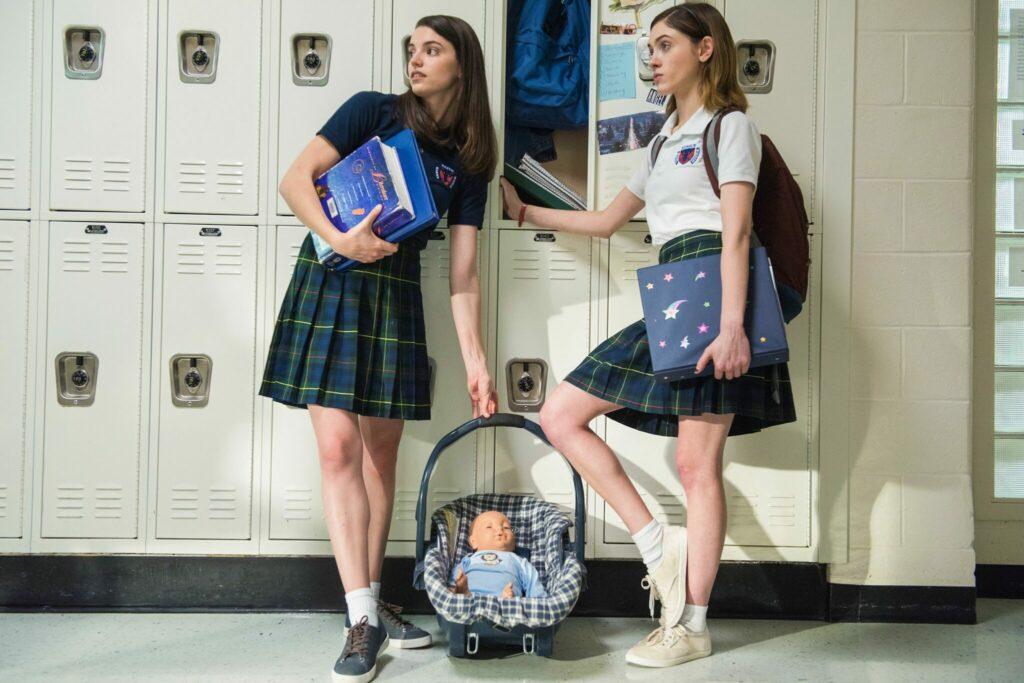 Alice steht gemeinsam mit einer Schülerin vor ihrem Spind. Beide halten Bücher in der Hand und eine Pupe im Kinderkorb liegt auf dem Boden in Yes, God, Yes - Böse Mädchen beichten nicht