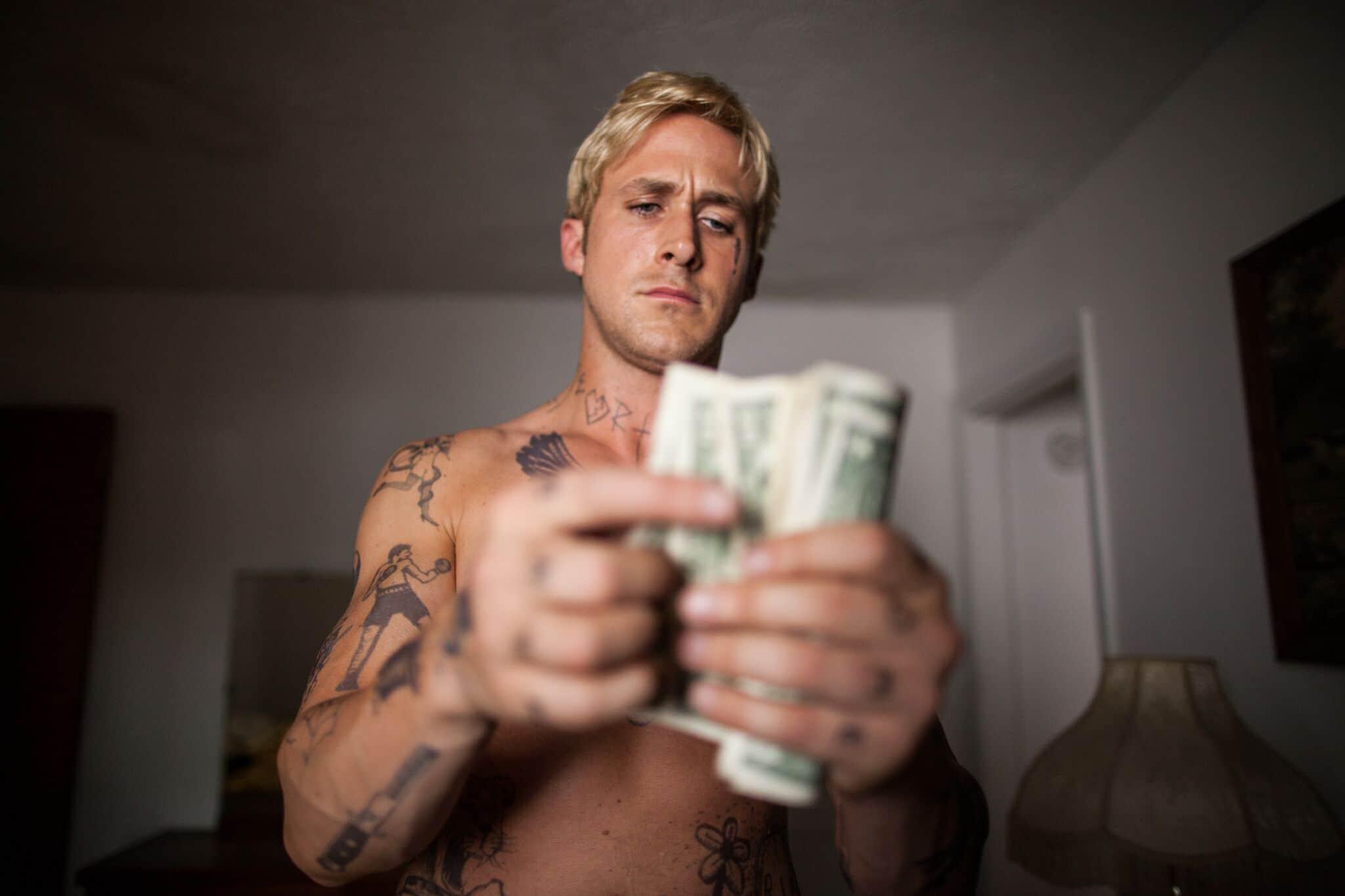 Luke (Ryan Gosling) steht oberkörperfrei in einem schlicht eingerichteten Raum und zählt konzentriert Geldscheine.