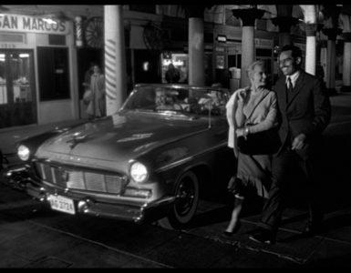 Susan und Miguel Vargas spazieren fröhlich über den Boulevard des Städchens, hinter ihnen das Cabrio von Linnekar