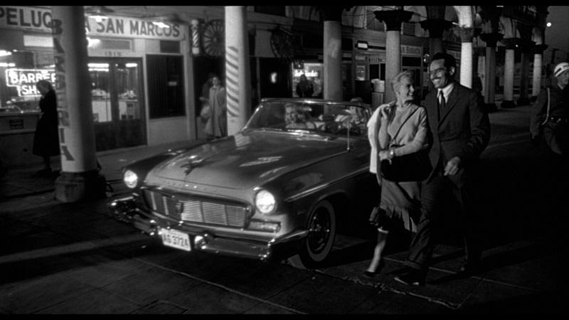 Susan und Miguel Vargas spazieren fröhlich über den Boulevard des Städtchens, hinter ihnen das Cabrio von Linnekar