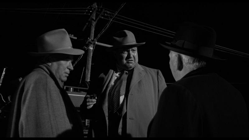 Quinlan bespricht sich mit zwei Männer des Justizministeriums in Im Zeichen des Bösen