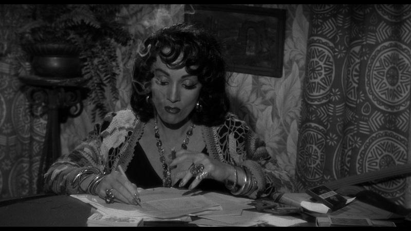 Zigeunerin Tanya (Marlene Dietrich) sitzt qualmend am Tisch und schaut in die Karten - Im Zeichen des Bösen