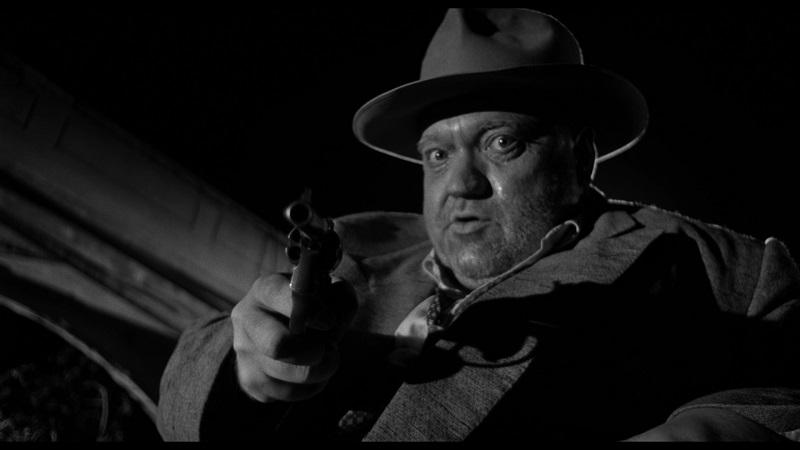 Hank Quinlan droht mit der Waffe und weit aufgerissenen Augen, der Wahnsinn spiegelt sich in seinem Blick - Im Zeichen des Bösen