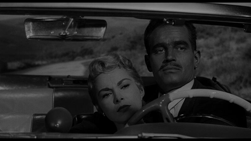 Man sieht durch die Frontscheibe ins Cabrio, wo Susan Vargas auf dem Schoß ihres Mannes Manuel liegt, der das Auto steuert.