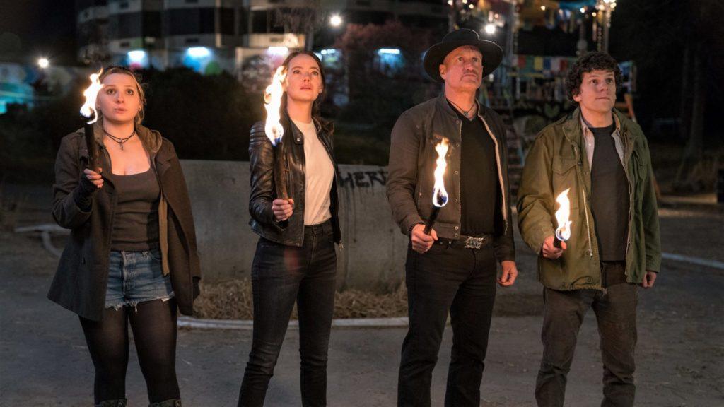 Little Rock (Abigail Breslin), Wichita (Emma Stone), Tallahassee (Woody Harrelson) und Columbus (Jesse Eisenberg) stehen bei Nacht mit Fackeln nebeneinander und sehen erstaunt nach oben.
