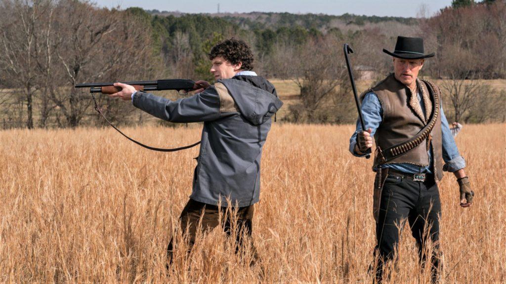 Columbus (Jesse Eisenberg) zielt mit seiner Schrotflinte, während Tallahassee (Woody Harrelson) seine Waffe prüft - beide stehen in einem Feld.
