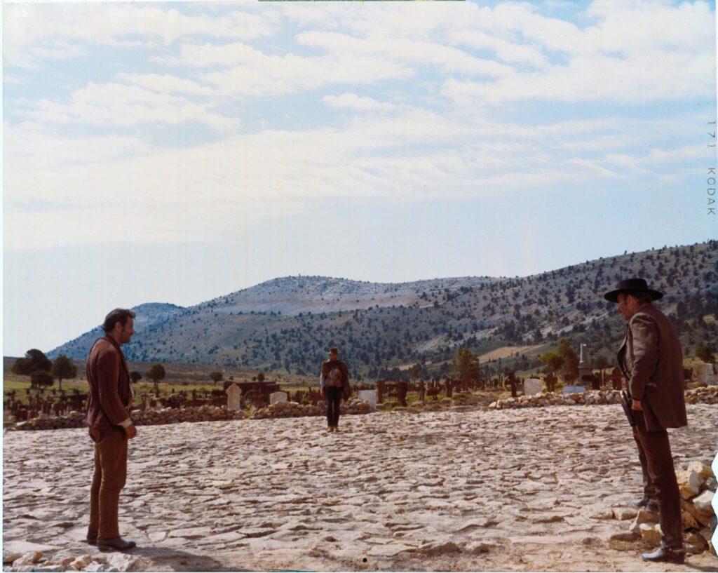 """Der deutsche Filmtitel heißt """"Zwei glorreiche Halunken"""", aber in dem Film geht es um drei Halunken und nicht nur um zwei. Tuco (Eli Wallach), der Blonde (Clint Eastwood) und Sentenza (Lee Van Cleef) stellen sich auf zum finalen Duell in der runden, arenaförmigen Fläche im Zentrum des Friedhofs. Tuco steht links im Bildvordergrund, Sentenza rechts. Der Blonde bildet die Mitte und steht im Bildhintergrund."""