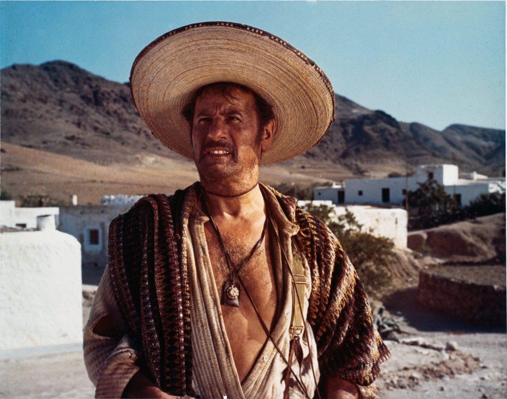 Das Bild zeigt den mexikanischen Banditen Tuco, gespielt von Eli Wallach, mit Sombrero und vor der Brust geöffneten Hemd vor der Kulisse eines mexikanischen Dorfes.