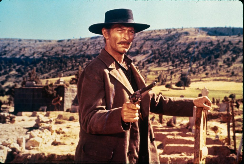 Sentenza (Lee Van Cleef) steht mit gezücktem Revolver kurz vor einer Schießerei. Er hat seine linke Hand auf einem Zaunpfahl abgestützt.