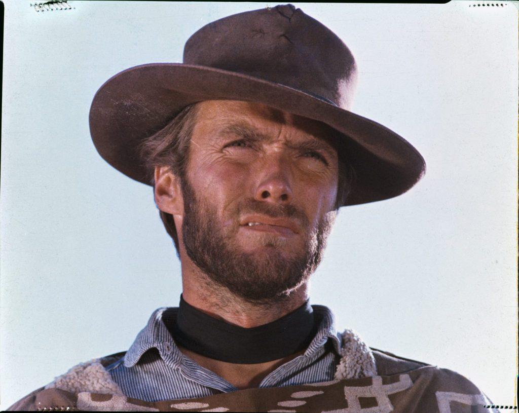 Eine Großaufnahme des Gesichts des Blonden (Clint Eastwood). Man sieht noch den Schulteransatz und erkennt, dass er bereits den Poncho trägt.
