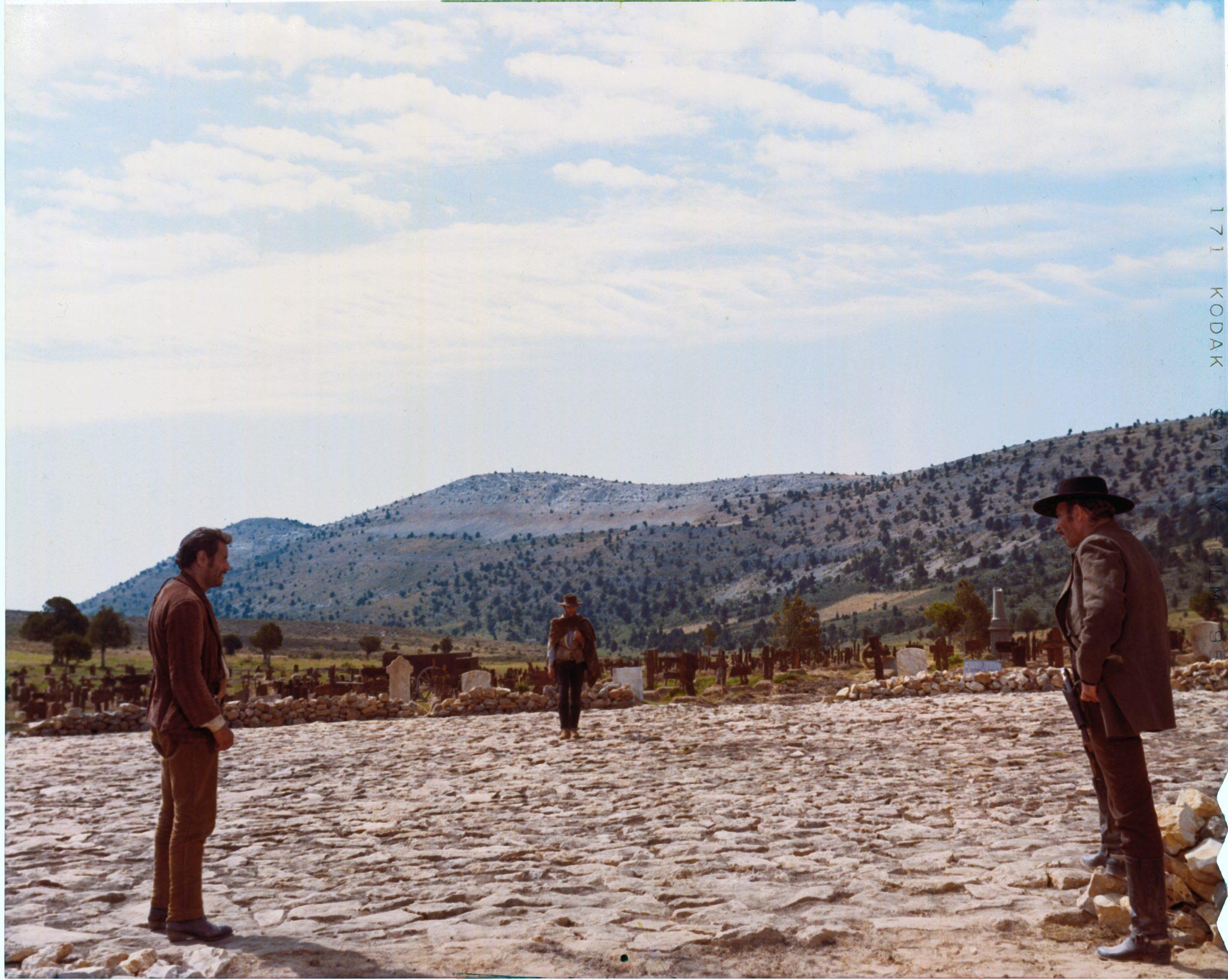 Tuco (Eli Wallach), der Blonde (Clint Eastwood) und Sentenza (Lee Van Cleef) stellen sich auf zum finalen Duell in der runden, arenaförmigen Fläche im Zentrum des Friedhofs. Tuco steht links im Bildvordergrund, Sentenza rechts. Der Blonde bildet die Mitte und steht im Bildhintergrund.