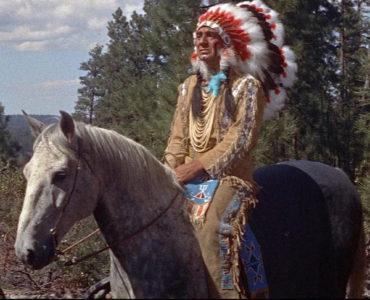 Häuptling Red Cloud, gespielt von Eduard Franz, sitzt in Zwischen zwei Feuern in vollem Federschmuck auf einem Pferd.
