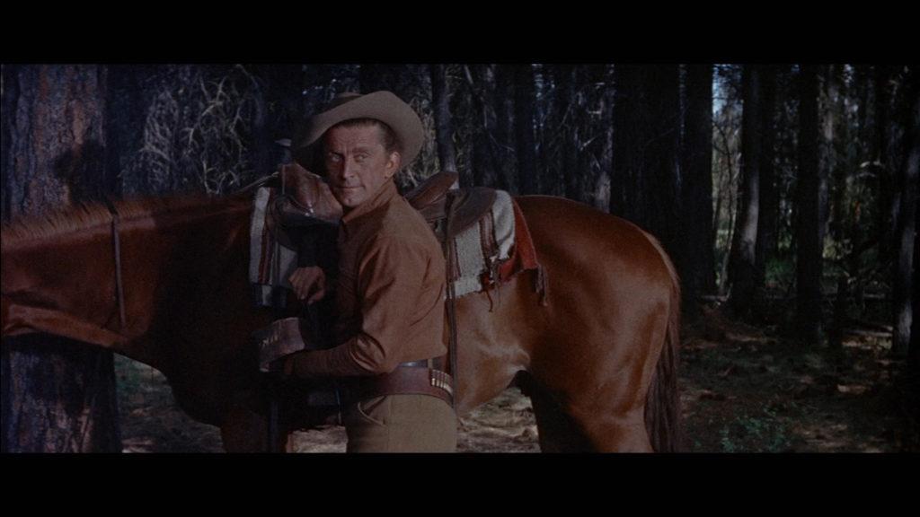 Der von Kirk Douglas gespielte Johnny Hawks steht im Wald vor seinem braunen Pferd.