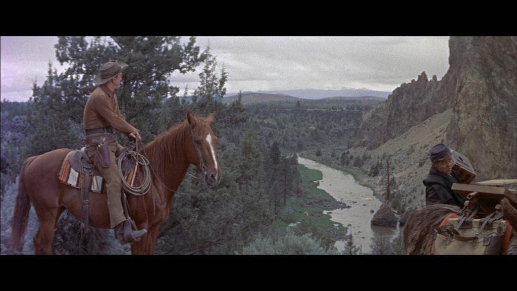 Am linken Bildrand sitzt der von Kirk Douglas gespielte Johnny Hwaks auf seinem Pferd und betrachtet die weite Flusslandschaft. Ganz rechts schultert Elisha Cook als Briggs seine Kamera.