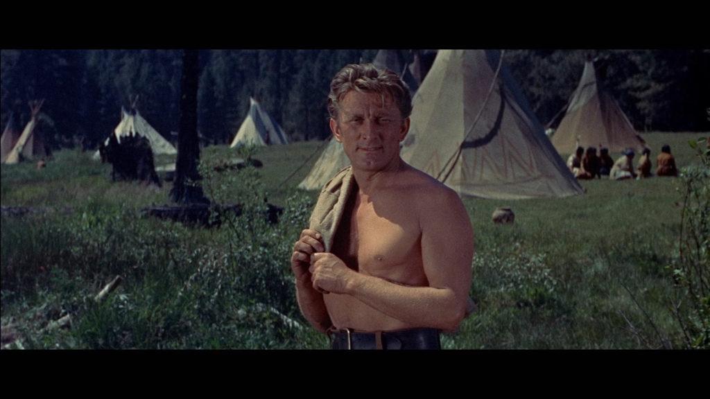 Kirk Douglas steht in Zwischen zwei Feuern als Johnny Hawks mit freiem Oberkörper im Indianerlager.