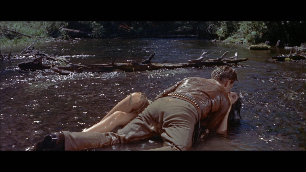 Johnny Hawks, gespielt von Kirk Douglas, wälzt sich mit Häuptlingstochter Onahti, gespielt von Elsa Martinelli, im Flussbett.
