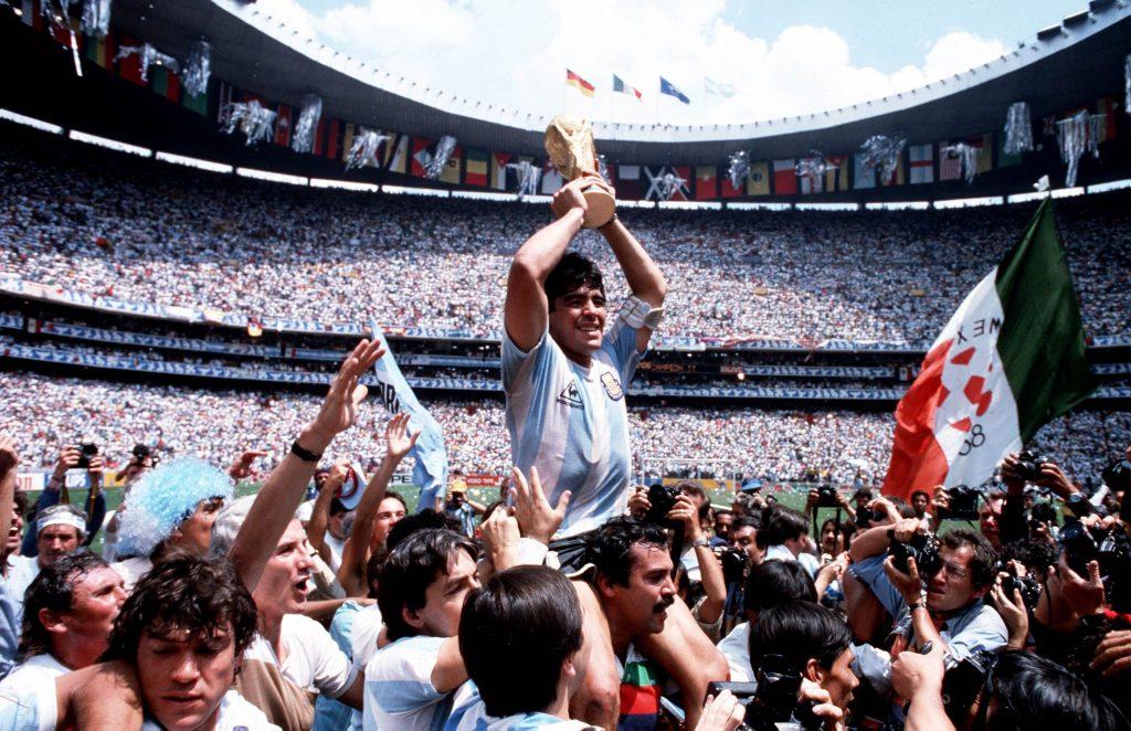 Diego Maradona streckt einen Pokal in die Luft, umringt von Leuten