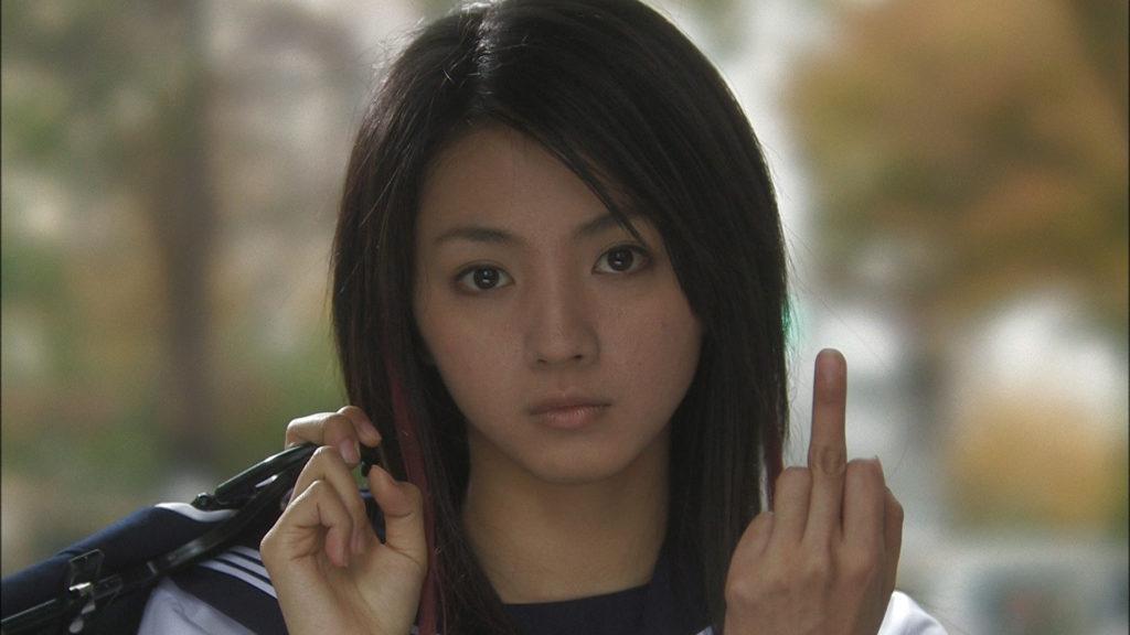 In Love Exposure zeigt Yoko in Schuluniform und einer Tasche über der Schulter den Mittelfinger
