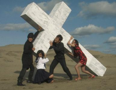 Yoko, ihre Mutter, Yu und sein Freund halten gemeinsam in der Wüste ein Kreuz hoch