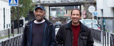 Die Hauptdarsteller von Alles außer gewöhnlich Vincent Cassel und Reda Kateb stehen grinsend auf einer Straße