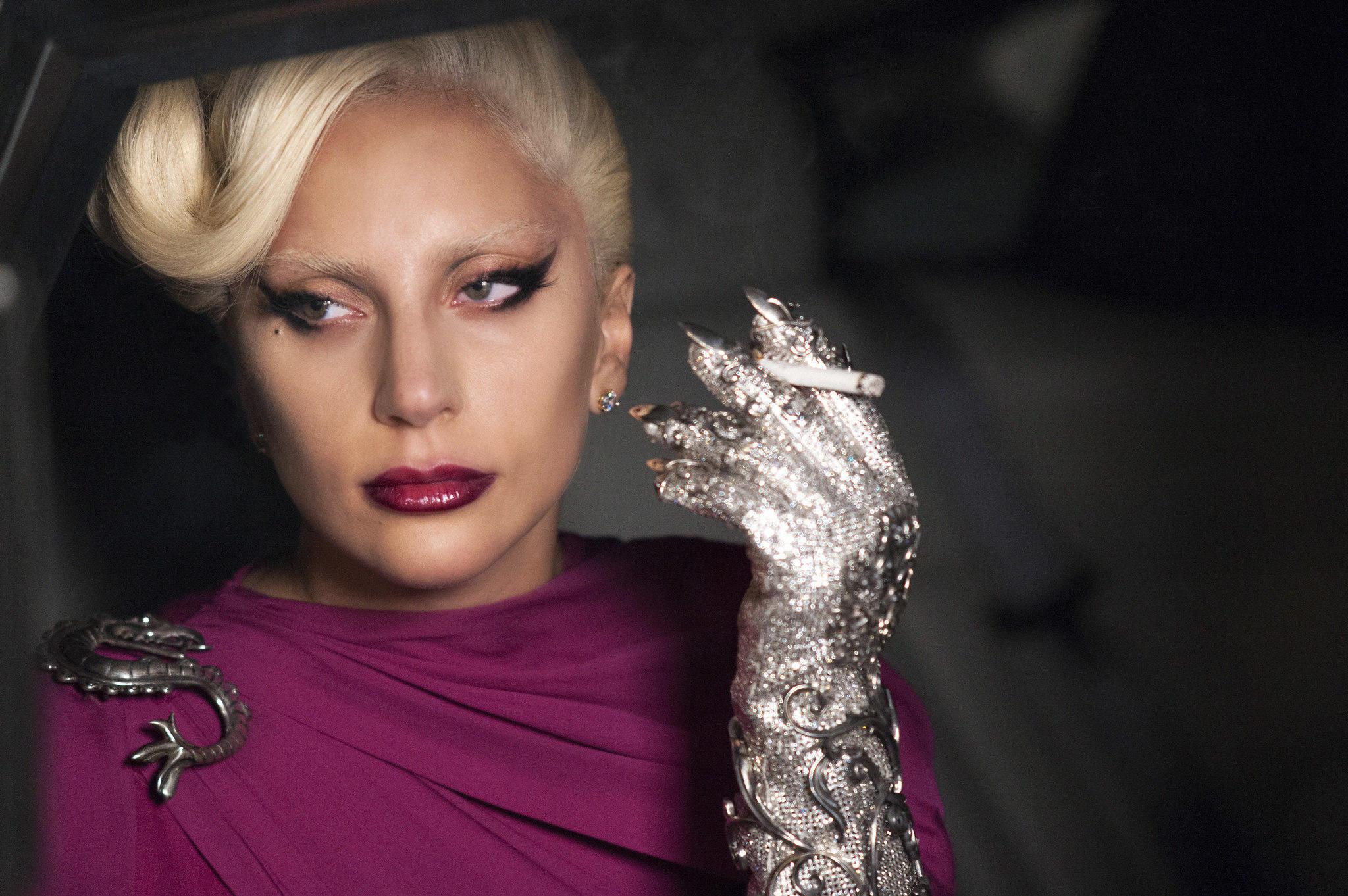 Lady Gaga in einem violetten Kleid mit Schlangenbrosche auf der Schulter, metallenem Handschuh samt Zigarette zwischen den Finger und blonden Haaren.