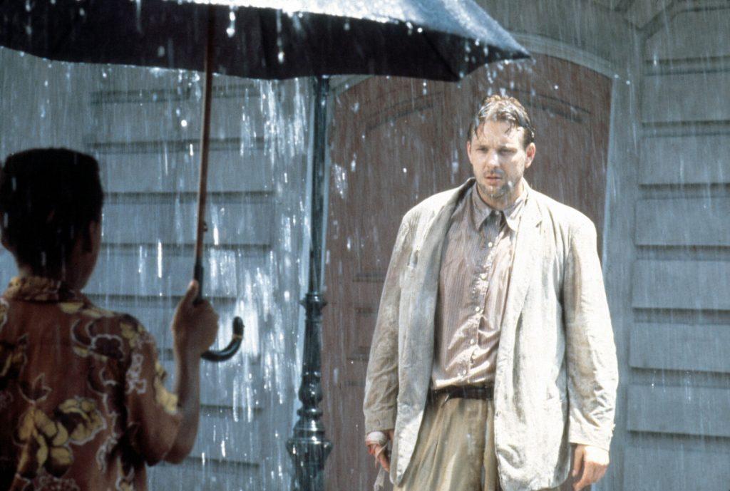 Harry Angel (Mickey Rourke) steht mit ernster Miene und durchnässt im Regen. Vor ihm steht eine Person mit dem Rücken zur Kamera und sie hält einen Regenschirm in der Hand