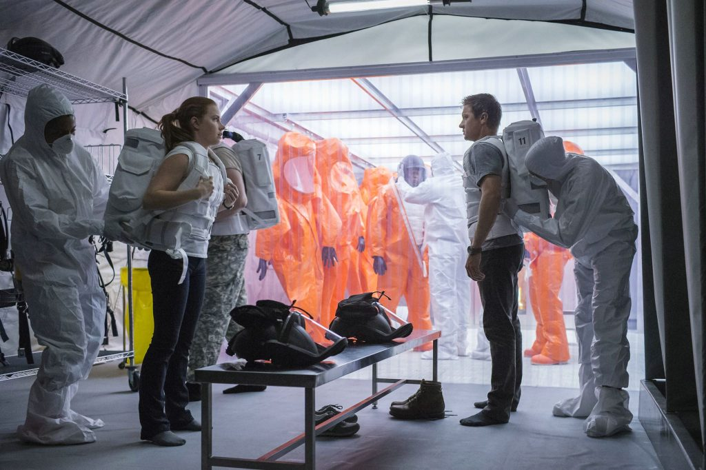 Amy Adams und Jeremy Renner stehen sich in einem Zelt gegenüber und bekommen Schutzanzüge angelegt.