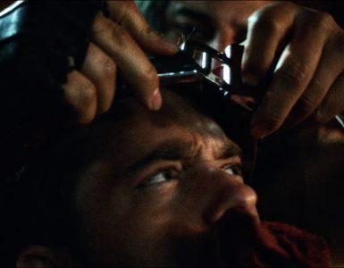 Artiks Hände werkeln mit Foltergeschirr über dem geknebelten Kopf Holtons