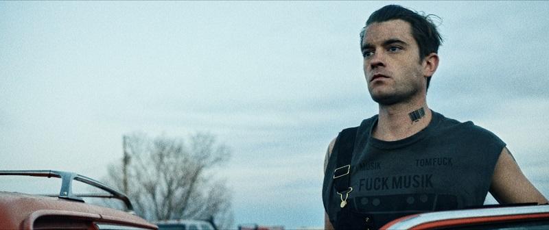 Holton steht an einer Autotür, schaut betroffen drein, hinter ihm der weite Himmel in Artik: Serial Killer