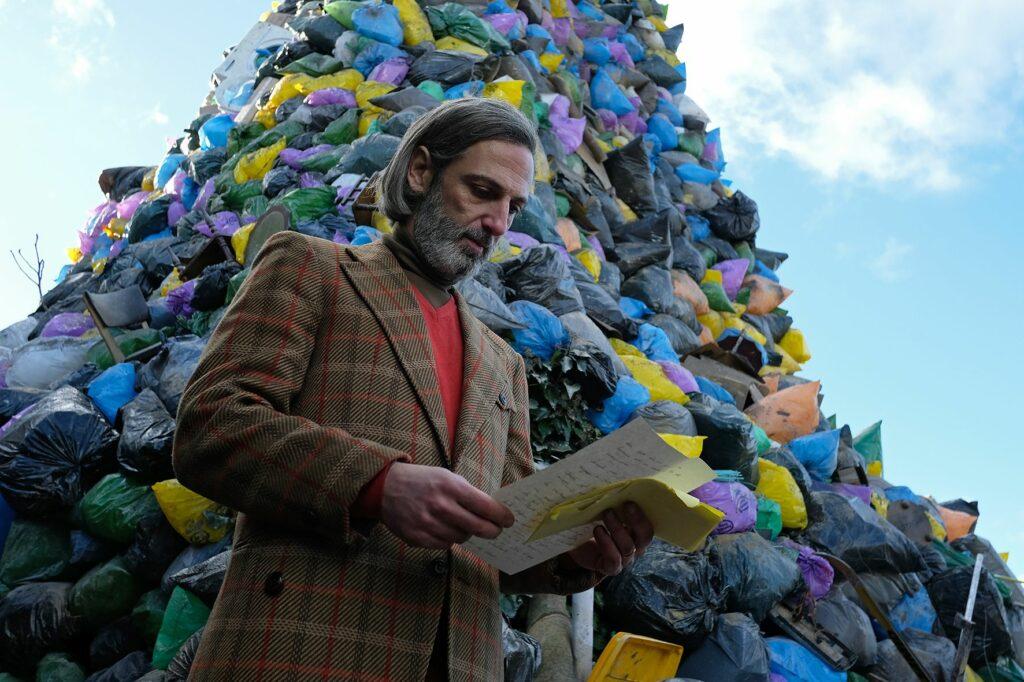 Ángel steht vor einem riesigen Berg an Müllsäcken und liest einen Brief in Die obskuren Geschichten eines Zugreisenden